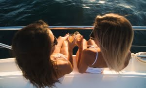 2 girls toasting on a boat